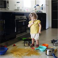 A 2 years old little girl posing in a kitchen in which she made the mess Stock Photo - Premium Rights-Managednull, Code: 877-08079192