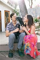 Young couple sitting on patio with dog licking face Stock Photo - Premium Royalty-Freenull, Code: 614-08081243