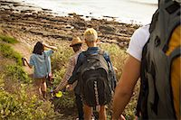 Group of friends walking down towards beach, rear view Stock Photo - Premium Royalty-Freenull, Code: 614-08081297