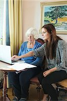 Grandmother and granddaughter using laptop together at home Stock Photo - Premium Royalty-Freenull, Code: 698-08081490