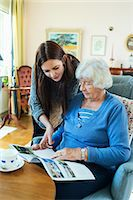 Grandmother and granddaughter reading magazine together in living room Stock Photo - Premium Royalty-Freenull, Code: 698-08081492