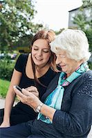 Young woman looking at grandmother using smart phone at park Stock Photo - Premium Royalty-Freenull, Code: 698-08081502