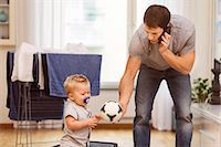 Father using mobile phone while giving ball to baby boy at home Stock Photo - Premium Royalty-Freenull, Code: 698-08081543