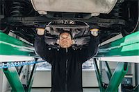 Male mechanic examining car on hydraulic lift in auto repair shop Stock Photo - Premium Royalty-Freenull, Code: 698-08081568