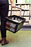 Low section of woman carrying basket in supermarket Stock Photo - Premium Royalty-Freenull, Code: 698-08081817