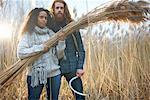 Couple harvesting wheat with scythe