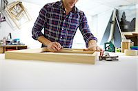 Mid adult man measuring frame on workbench in picture framers workshop Stock Photo - Premium Royalty-Freenull, Code: 649-08086959