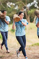 Woman running with log on boot camp obstacle course Stock Photo - Premium Royalty-Freenull, Code: 6113-08087928
