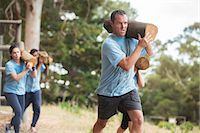 Determined man running with log on boot camp obstacle course Stock Photo - Premium Royalty-Freenull, Code: 6113-08087947