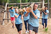 Determined people running with logs on boot camp obstacle course Stock Photo - Premium Royalty-Freenull, Code: 6113-08087967