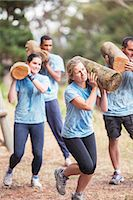 Determined people running with logs on boot camp obstacle course Stock Photo - Premium Royalty-Freenull, Code: 6113-08087970