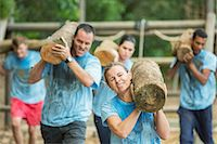 Determined people running with logs on boot camp obstacle course Stock Photo - Premium Royalty-Freenull, Code: 6113-08088045