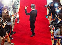 Celebrity arriving at red carpet event and waving at photographing paparazzi Stock Photo - Premium Royalty-Freenull, Code: 6113-08088158