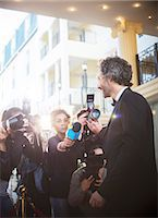 Celebrity being interviewed and photographed by paparazzi at event Stock Photo - Premium Royalty-Freenull, Code: 6113-08088164