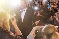 Smiling celebrity posing for paparazzi photographers at event Stock Photo - Premium Royalty-Freenull, Code: 6113-08088208
