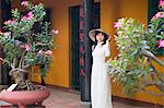 Woman wearing ao dai dress at Giac Lam Pagoda, Ho Chi Minh City, Vietnam, Indochina, Southeast Asia, Asia