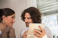 Mid adult couple using a digital tablet, Munich, Bavaria, Germany Stock Photo - Premium Royalty-Freenull, Code: 6121-08106515