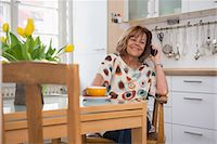 Happy senior woman having a cup of tea and talking on cell phone in kitchen, Munich, Bavaria, Germany Stock Photo - Premium Royalty-Freenull, Code: 6121-08106578