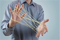 Mid section view of a man's hands making a cats cradle with string, Bavaria, Germany Stock Photo - Premium Royalty-Freenull, Code: 6121-08106839
