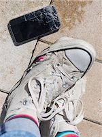 Person's leg with torn canvas shoes and cracked smartphone, Bavaria, Germany Stock Photo - Premium Royalty-Freenull, Code: 6121-08107029