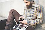 Mid adult man sitting outdoors with dog, using smartphone and digital tablet