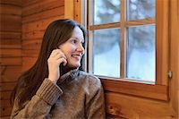 Portrait of young woman chatting on smartphone and looking out of window, Posio, Lapland, Finland Stock Photo - Premium Royalty-Freenull, Code: 649-08118766