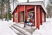 Portrait of young female skier drinking coffee on cabin porch, Posio, Lapland, Finland Stock Photo - Premium Royalty-Freenull, Code: 649-08118770