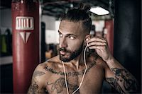 Male boxer inserting ear phones in preparation for training Stock Photo - Premium Royalty-Freenull, Code: 614-08119875