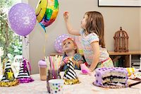 popping (bursting not corks or pimples) - Two girls sitting at birthday party table with cake playing with balloons Stock Photo - Premium Royalty-Freenull, Code: 614-08120076