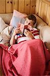 Boy reading book on sofa Stock Photo - Premium Royalty-Free, Code: 6102-08120123