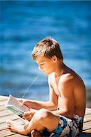 preteen boy shirtless - Boy reading book on jetty Stock Photo - Premium Royalty-Freenull, Code: 6102-08120130