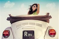female rear end - Young woman wearing sunglasses with wind in hair, sitting in a vintage, convertible Volkswagen Beetle, Italy Stock Photo - Premium Royalty-Freenull, Code: 600-08122180