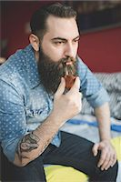 Young bearded man smoking pipe on bed Stock Photo - Premium Royalty-Freenull, Code: 649-08125278