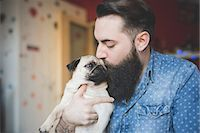 Young bearded man kissing dog in arms Stock Photo - Premium Royalty-Freenull, Code: 649-08125280