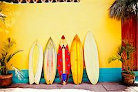 Five patterned, vintage surfboards leaning against a wall Stock Photo - Premium Royalty-Freenull, Code: 673-08139247