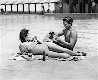 1930s 1940s COUPLE WEARING BATHING SUITS SITTING  RELAXING POOL SIDE DRINKING BEER Stock Photo - Premium Rights-Managednull, Code: 846-08140036