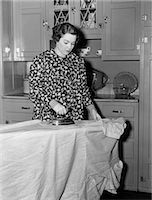 1930s 1940s WOMAN WEARING PRINTED SMOCK APRON STANDING IRONING BOARD PUSHING ELECTRIC IRON Stock Photo - Premium Rights-Managednull, Code: 846-08140042