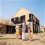 1970s FAMILY OF FOUR MAN WOMAN BOY GIRL LOOKING AT NEW HOME UNDER CONSTRUCTION