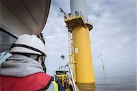 supervising - Engineers winching parts up to wind turbine on offshore windfarm Stock Photo - Premium Royalty-Freenull, Code: 649-08145370