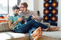 Male couple relaxing on sofa together Stock Photo - Premium Royalty-Freenull, Code: 614-08148655