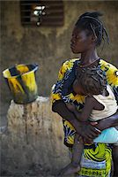 Mother holding child in arms while nursing, black and yellow patterns, Gaoua, Poni Province, Burkina Faso Stock Photo - Premium Rights-Managednull, Code: 700-08169189