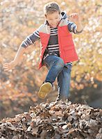pile leaves playing - Enthusiastic boy jumping over pile of autumn leaves Stock Photo - Premium Royalty-Freenull, Code: 6124-08170409