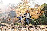 Family holding hands and walking in autumn leaves