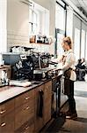 Full length of female barista using coffee machine at cafe