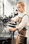 Young female barista using coffee maker at cafe