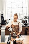 Female barista looking away while preparing coffee at cafe counter