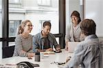 Happy senior businesswoman discussing with colleagues in board room
