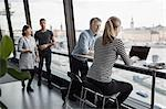 Business people discussing by window in office