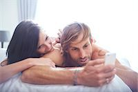 Couple relaxing on bed texting with cell phone Stock Photo - Premium Royalty-Freenull, Code: 6113-08171378