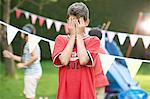 Boy covering his eyes for hide and seek with sister and brother in garden